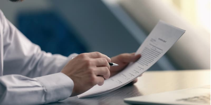 A closeup of a lawyers reading a legal document and making notes with a pen.