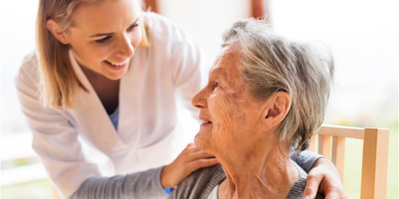 An aged care nurse and an older lady smiling at each other and chatting.