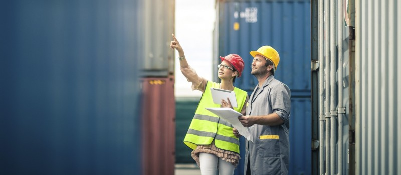 A male and female engineer wearing hard hats and pointing at a building.
