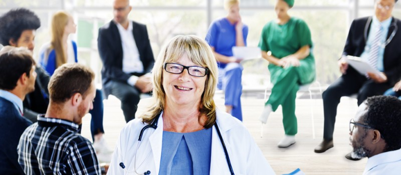 A female doctor smiling at the camera - behind her are other doctors in a meeting.