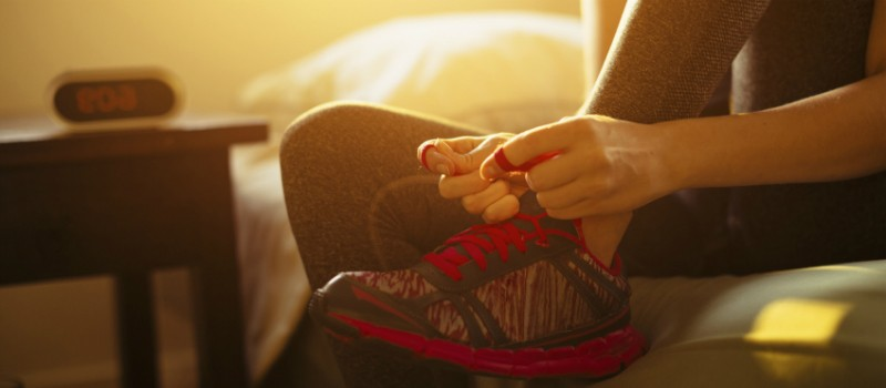 A person tying up their shoe laces in preparation to go for a run.