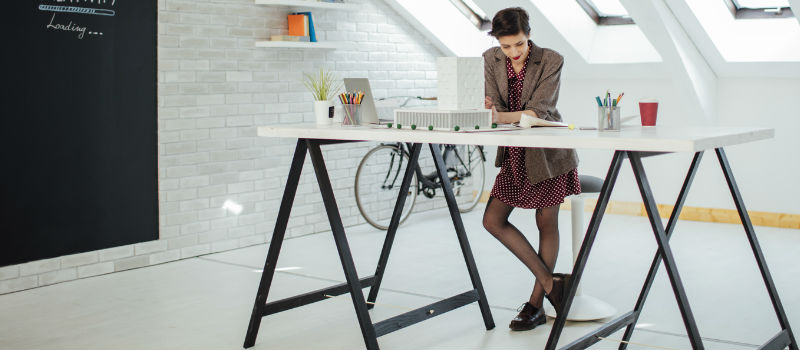 A female professional working at a standing desk in a modern office.