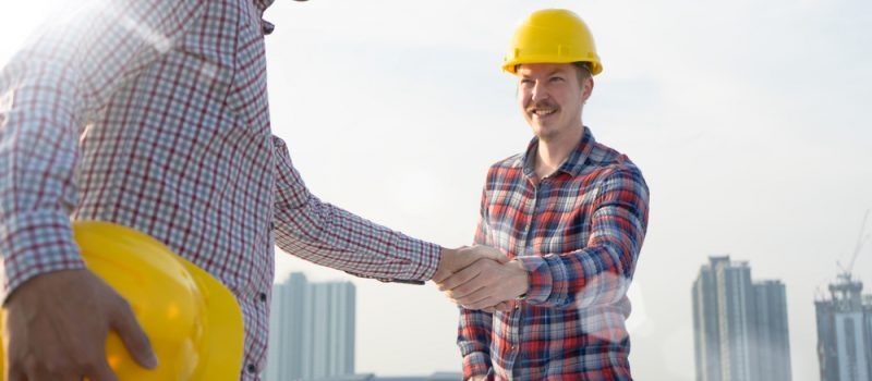 Two engineers shaking each other's hands at a project site.