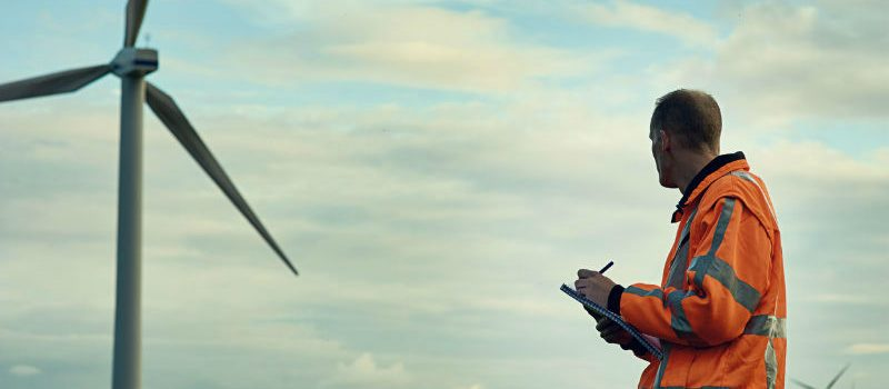 An engineer assessing machinery at a wind farm.