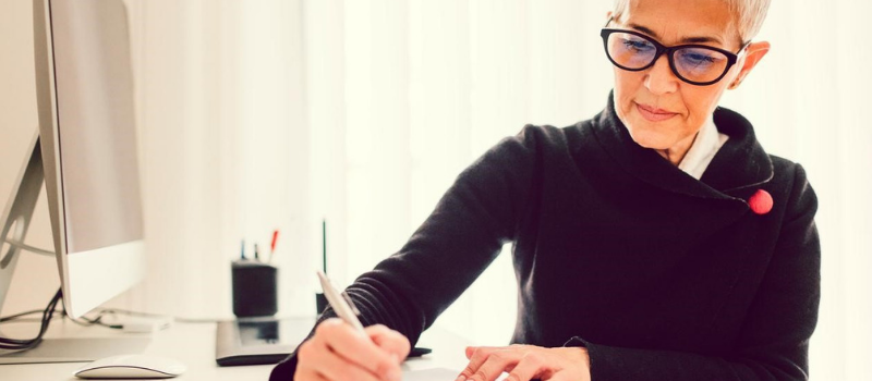 A female business professional sitting at a desk, writing.