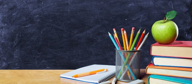 School items on a wooden desk: notepad, pencils, books and an apple.