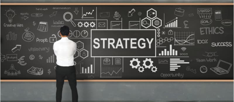 "A man standing in front of a blackboard that says ""strategy""."